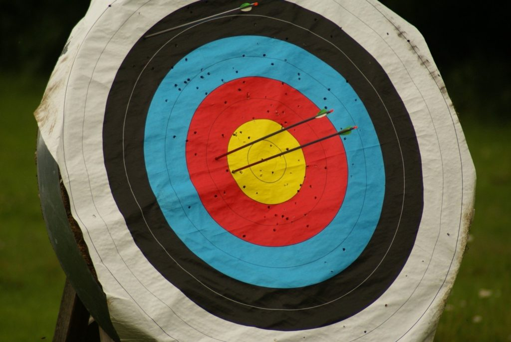 An archery target with arrows sticking out the bullseye